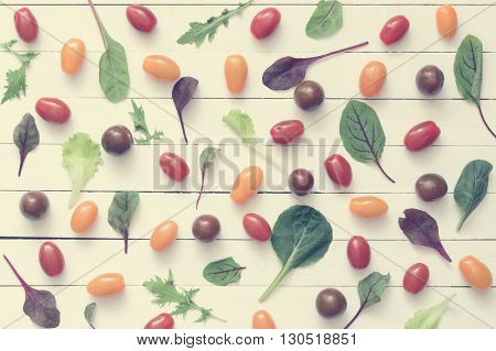 Cherry tomatoes and green salad leaves on white wooden background. Top view, flat lay food. Vintage toning