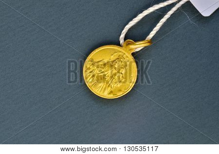 Golden scapular pendant traditionally given for first communion gift. Macro image.