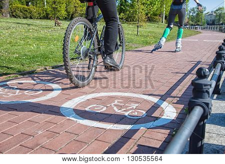 girl roller-skating and bicycler on the bike path on sunny spring day