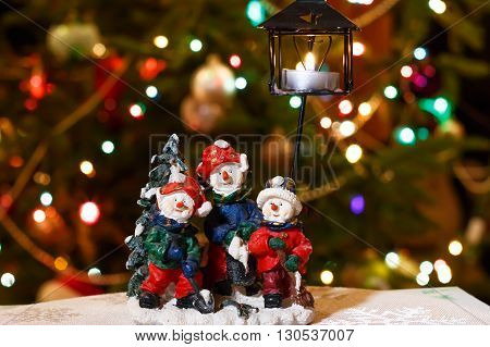 Merry snowmen candleholder with burning candle in front of Christmas tree lights that are defocused, blurred background
