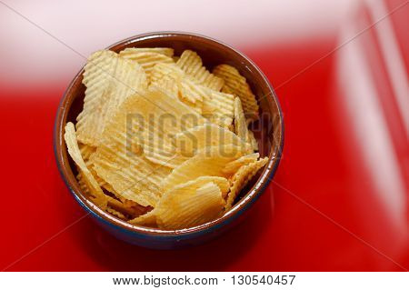 Rippled potato chips in a bowl closeup