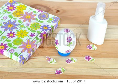 Decoupage Easter egg, glue, napkins with a floral pattern on a natural wooden background
