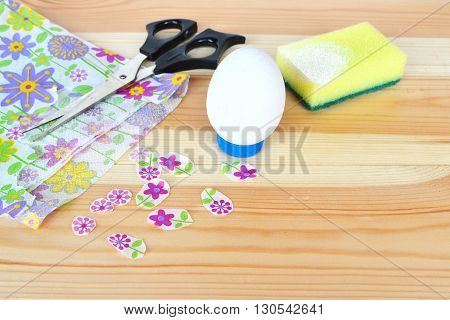 White painted wooden Easter egg, scissors, napkin, floral fragments, sponge with white acrylic paint on wooden background, decoupage set