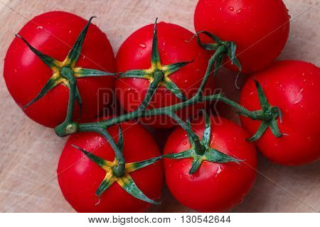 Branch of fleshy tomatoes on a wooden table closeup