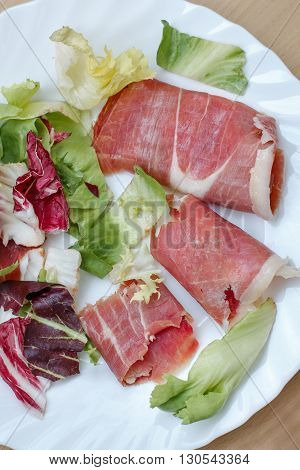 Vertical closeup of slices of rolled cured pork ham jamon with lettuce