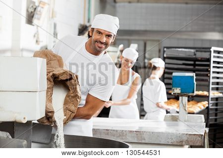 Smiling Male Baker Pouring Flour In Kneading Machine