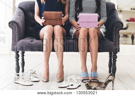 At the retail store. CLose-up of young women with perfect legs holding leather purses while sitting on sofa at the shopping store