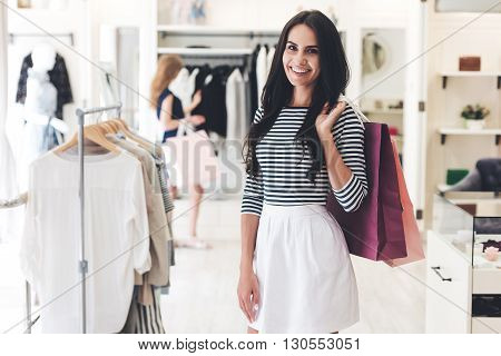 Expert in shopping. Beautiful young woman with shopping bags looking at camera with smile while standing at the clothing store