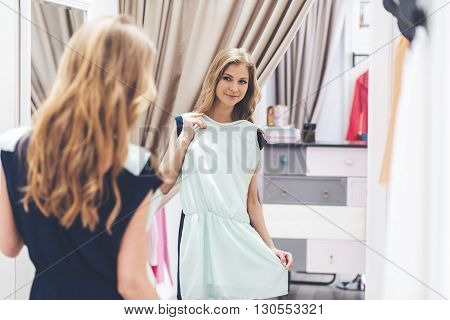 This dress is perfect! Rear view of beautiful young woman trying on dress and looking at her reflection in the mirror while standing in fitting room at the store