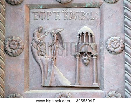 PISA, ITALY - JUNE 06, 2015: Temptation of Christ on the San Ranieri gate of the Cathedral St. Mary of the Assumption in Pisa, Italy on June 06, 2015
