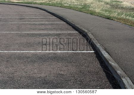 White lines form parking spaces on black asphalt.