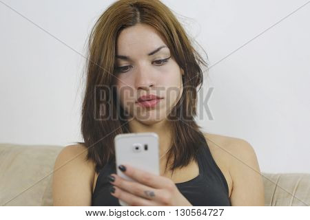 Woman using new mobile phone with one hand at home sitting in sofa