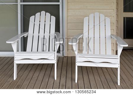 Two white wooden adirondack chair on old weathered front porch at white bungalow