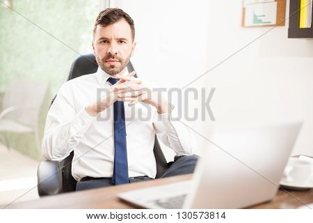 Portrait of a young Hispanic CEO looking powerful and confident while sitting in front of his office desk poster