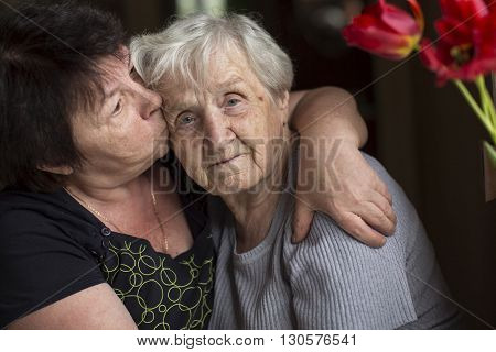 Woman kissing his old mother. Care for the elderly.