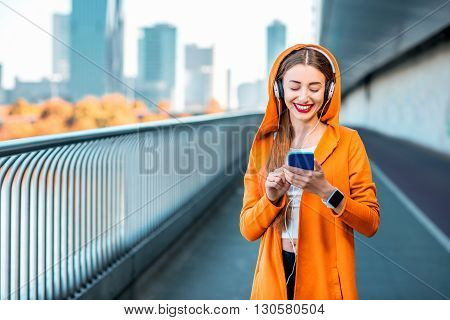 Young sport woman in yellow sweater listening to the music with smart phone on the modern bridge with skyscrapers on the background. Morning exercise in megacity