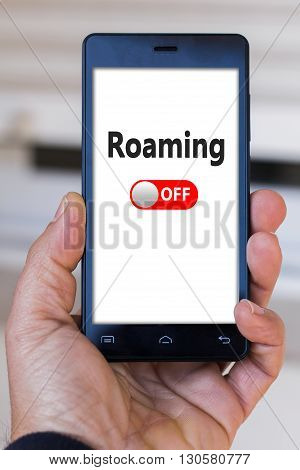 Hand holding black smartphone with roaming on words on white screen