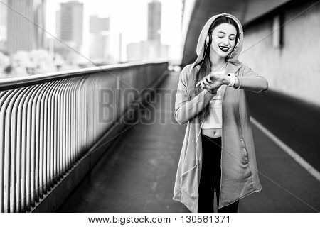 Young sport woman in yellow sweater listening to the music with smart watch on the modern bridge with skyscrapers on the background. Morning exercise in megacity