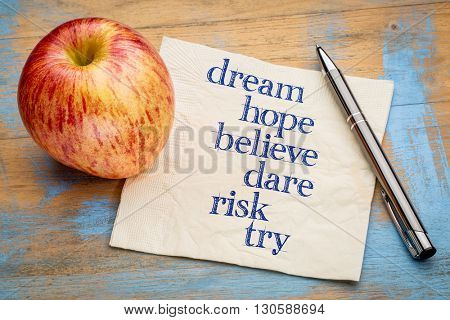 dream, hope, believe, dare, risk and try - handwriting on a napkin with a fresh apple
