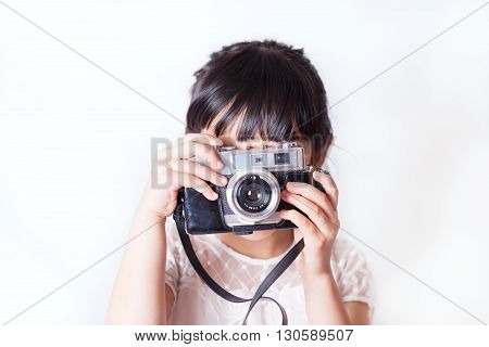 Young person photographing with a vintage camera.