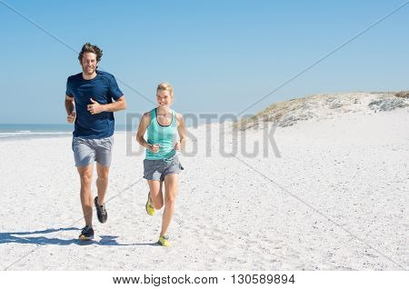 Couple runners exercising on a sandy beach with copy space. Couple running on beach training for marathon run. Athletic attractive man and young woman jogging in a summer day.