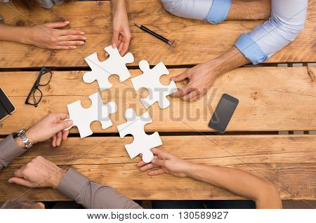 Close-up of businesspeople solving jigsaw puzzle. Closeup of business people wanting to put four pieces of puzzle together. Businesspeople trying to solve problem with the help of jigsaw puzzle.