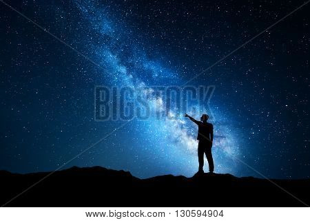 Silhouette of a standing young man pointing finger in night starry sky on the background of blue Milky Way. Colorful night landscape. Beautiful Universe travel background with sky full of stars