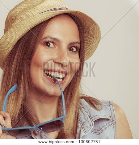 Happy glad woman holding sunglasses. Seductive and flirty girl. Summer vacation holidays.