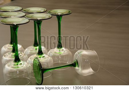 Classic Green Stemmed Wine Glasses Overturned in a Triangular Fashion poster