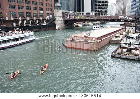 Clark Street bridge on the Chicago river in Chicago, connecting the Loop and Near north side. People are seen having water ride on boats. Skyscrapers are seen on the background.