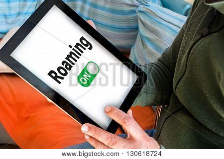 Hand holding black tablet with roaming on words on white screen (Turn on data roaming)