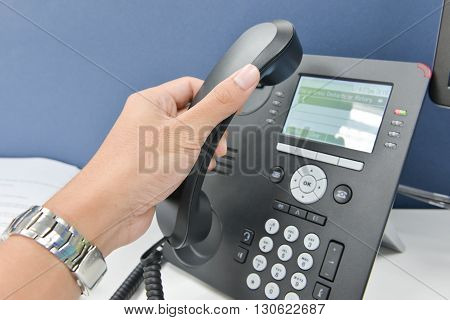 Human hand is picking up the telephone