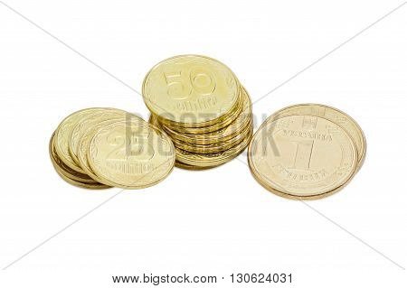 Three stacks of coins of the Ukrainian hryvnia different denominations closeup on a light background