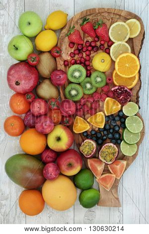 Large fresh fruit collection on an olive wood board over distressed wooden background. High in antioxidants, anthocyanins, vitamins and dietary fiber.