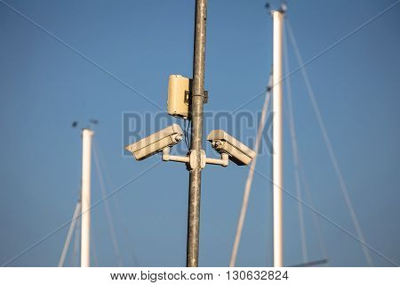 Pair of outdoor security cameras in yachting harbor