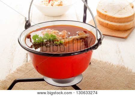 hungarian carp soup in a small red kettle and sour salad