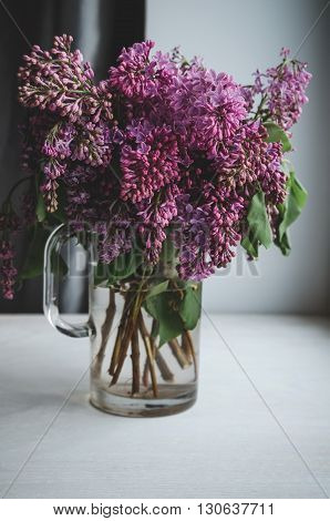 Still life with blooming spring branches of lilac flowers in vase on dark background. Home decoration in a rustic style. Violet bouquet on white windowsill in room.