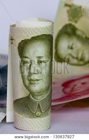 Chinese renminbi bank notes rolled up ready for use.