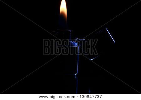 black gasoline lighter with flame on dark background poster
