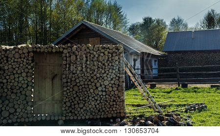 Door To Woodpile In The Background Of Green Grass