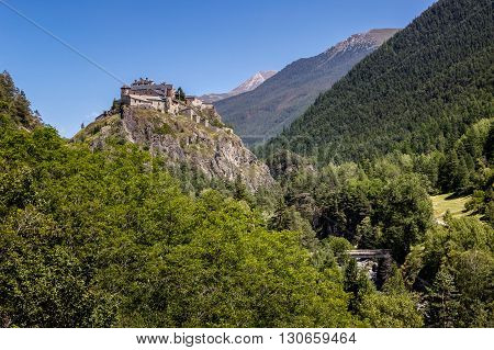 Middle Age castle (13th century) atop a hillside in the Queyras region of the Southern French Alps. It is surrounded by a deep forest (Hautes-Alpes, France)
