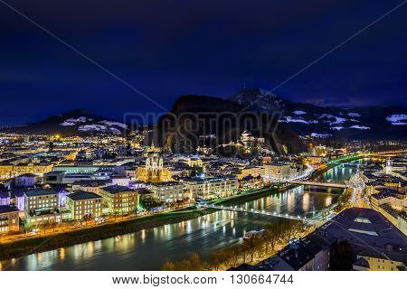 Panoramic view of the historic city of Salzburg with Hohensalzburg Fortress and Salzach river at dusk.