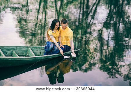 Young Girl And Man Sitting Together In Old Wooden Boat On River.