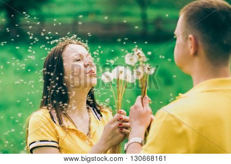 Couple In Love Blowing Cheerfully Blowballs Flowers