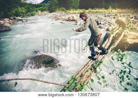 Man Traveler crossing over river on woods outdoor Lifestyle Travel extreme survival concept