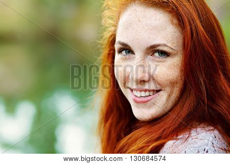 portrait af a beautiful redhead woman outdoors. stylish romantic young girl on a walk in the park with red hair and freckles