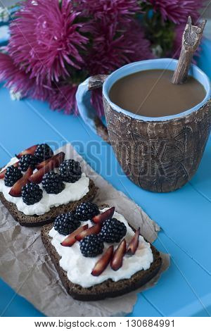 Andwiches With Sweet Cheese And Berries, A Cup Of Coffee And A Bouquet Of Asters In Blue Wooden Back