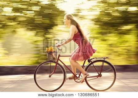 motion blur young woman in a dress rides a bike in a summer park. Active people outdoors