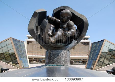 ODESSA, UKRAINE - MAY 8, 2010: Statue of the Golden Baby and Cruise Terminal of Sea Port in Odessa, Ukraine. Golden child - a bronze sculpture by sculptor Ernst Neizvestny. Four-meter figure of a boy became the world's largest baby figure.