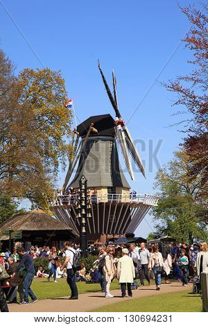 LISSE, NETHERLANDS - MAY 5, 2016: Tourists at the windmill in the Keukenhof Park in Lisse, Netherlands. It is popular flower garden which is visited by million tourists from all around world.